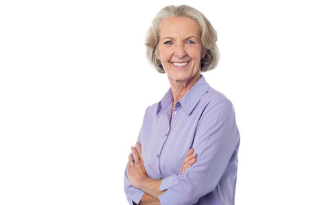 Isolated aged lady posing with crossed arms photo
