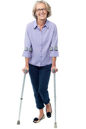松葉杖の助けを借りて歩く年配の女性