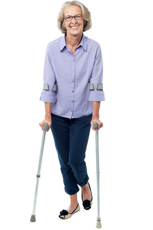 Senior woman walking with the help of crutches photo