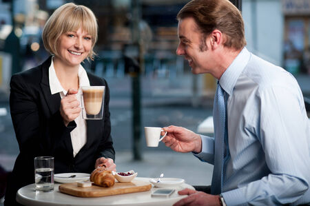Business partners toasting coffee at cafe photo