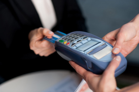 debit card: Businesswoman swipes her credit card to make the payment Stock Photo
