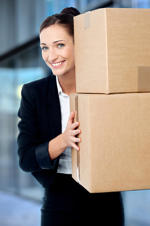 Smiling business executive carrying boxes photo