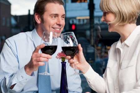 Attractive couple raises a glass of red wine in cafe photo