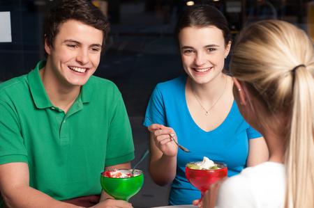 relishing: Friends of three enjoying meal at restaurant Stock Photo