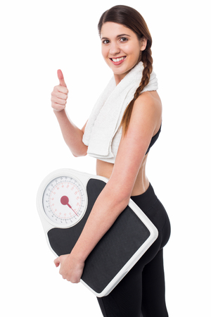 thumps up: Healthy young woman with a weight scale and thumps up