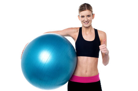 Fitness trainer with aerobic ball and showing thumbs sign