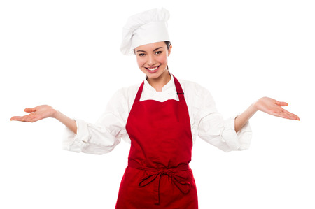 warm welcome: Female chef standing with open palms, warm welcome gesture.