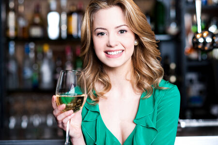 Attractive young girl enjoying champagne in a pub photo