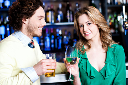 Cheerful young couple having cocktail at restaurant bar photo