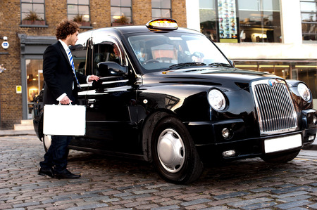 Taxi cab driver communicating with male passenger photo