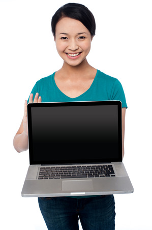 Casual smiling female sales executive promoting new laptop photo