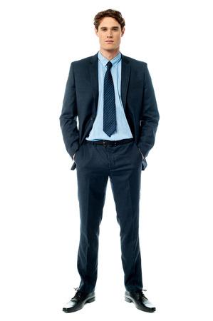 Zakenman poseren met de handen in de zak op wit wordt geïsoleerd Stockfoto