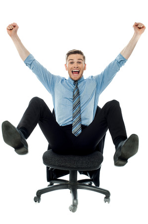 Excited business man with arms raised while sitting Stock Photo