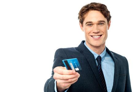 debit card: Smiling businessman handing over his debit card
