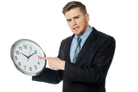 Homme d'affaires montrant une horloge isolé sur blanc Banque d'images