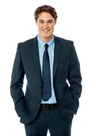 Giovane uomo d'affari in piedi con le mani nelle tasche