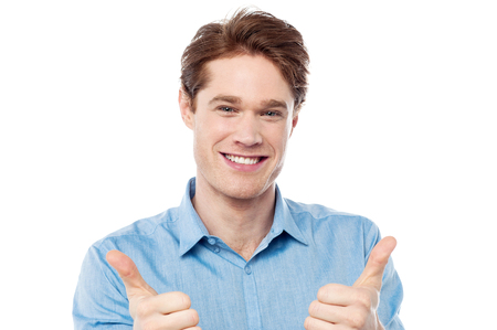 posing  agree: Cool young man showing double thumbs up Stock Photo