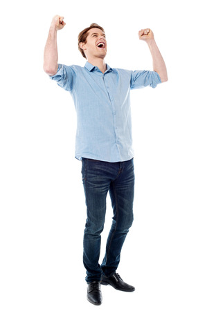exhilaration: Handsome young man raising his arms in excitement