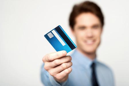 若い企業の男彼のデビット カードを示す