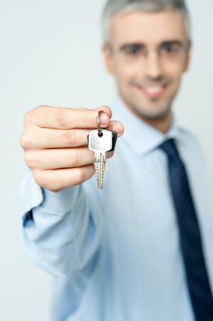 Smiling businessman holding a house key photo