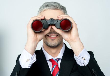 Businessman viewing through binoculars Stock Photo