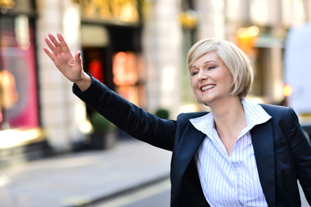 business for the middle: Middle aged business woman calling for taxi