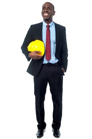 Civil engineer holding yellow helmet and looking away photo