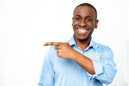 facing the camera: Guy pointing away while facing camera Stock Photo