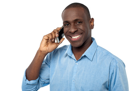 Smiling young man communicating through mobile phone photo