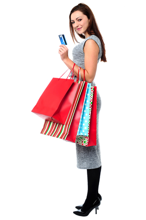 Fashionable woman posing with shopping bags and credit card photo