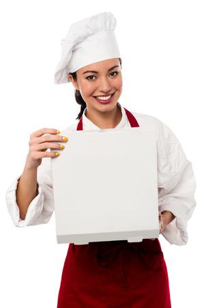 pizza box: Hermosa mujer joven cocinero que sostiene una caja de pizza