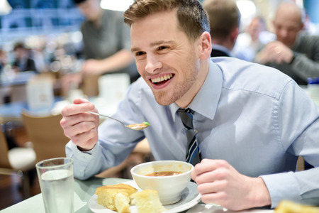 breakfast food: Young handsome businessman eating lunch in a cafe