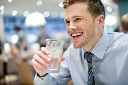 man with glasses: Handsome young man in a bar and drinking water