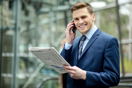Businessman talking on the phone while reading the newspaper photo