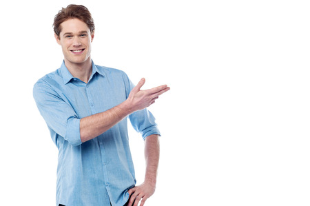 Young smiling man presenting copy space area