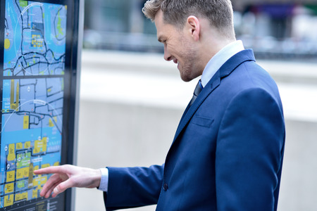 Businessman at bus stop reading a timetable photo