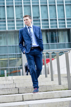 Young businessman coming down stairs with hands in pockets photo