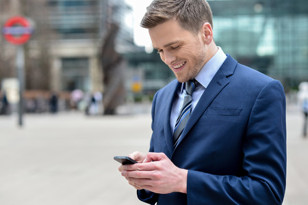 secretary phone: Attractive businessman using his cell phone in street
