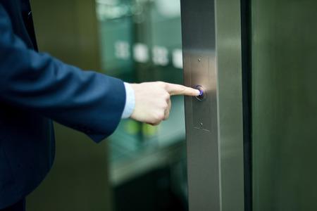people in elevator: Businessman pressing elevator button