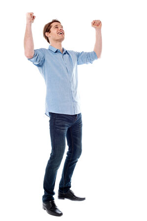 Handsome young man raising his arms in excitement photo