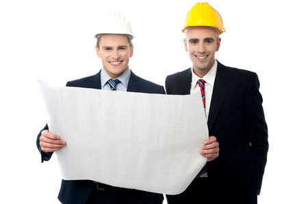 Smiling engineers in hard hats with blueprints photo