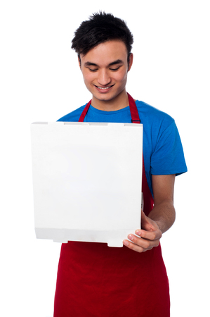Smiling male chef holding an opened pizza box photo
