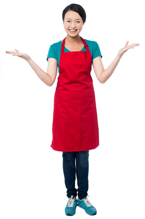 Smiling young female chef standing with open palms photo