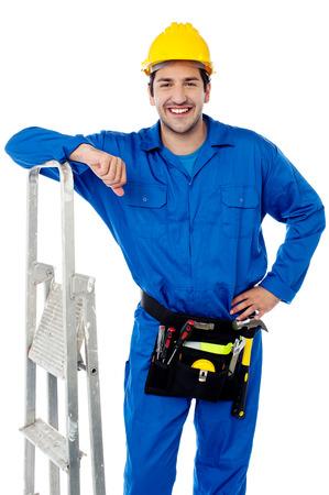 Smiling handyman posing near his step ladder photo