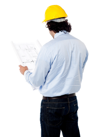 Back view of male engineer reviewing construction site plan photo