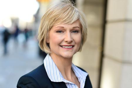 オフィスの外に立っている女性高齢者中間の笑みを浮かべて 写真素材
