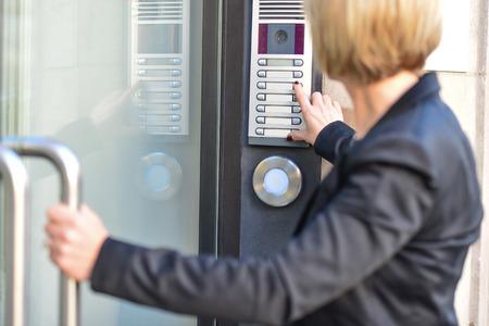 中年女性がインターホンのボタンを押す 写真素材