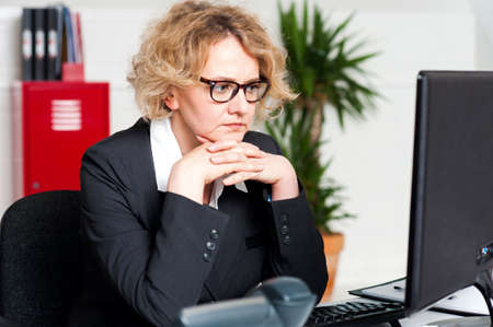 Serious businesswoman sitting with hands on chin photo