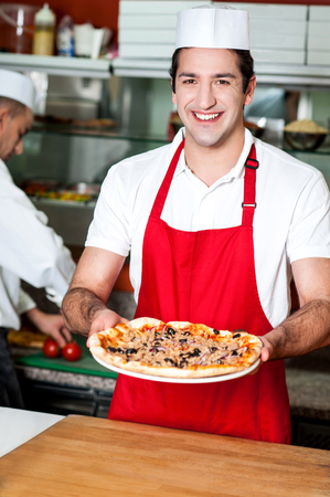 Smiling young male chef handing over pizza photo