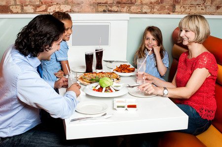 Happy couple and their children sitting in restaurant photo